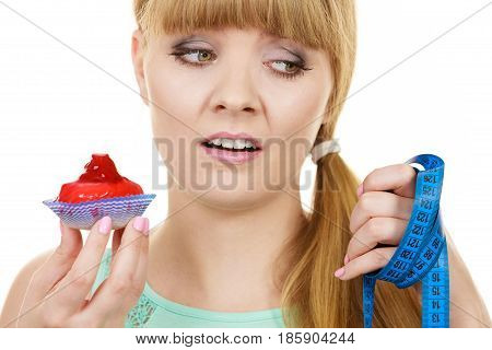 Woman undecided with blue measuring tape holds in hand cake cupcake trying to resist temptation. Weight loss diet dilemma gluttony concept.