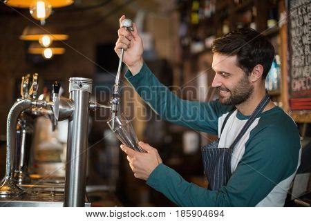 Happy bartender pouring beer from tap in glass at bar