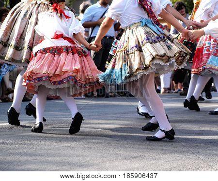 Little girls dancing on street in traditional folk attire