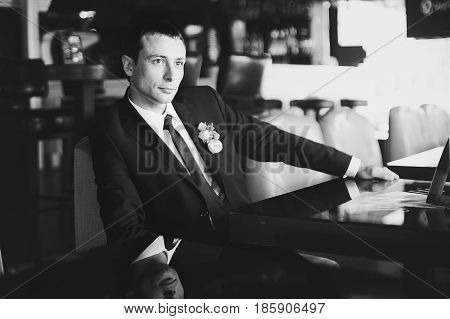 Black and white picture of thoughtful groom sitting at the table in restaurant