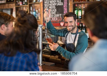 Smiling bartender pouring beer in glass for customers at bar
