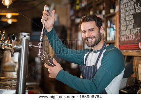Portrait of bartender pouring beer from tap in glass at bar
