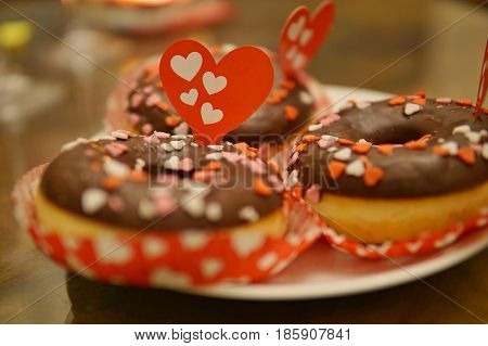Macro detail of sweet donuts covered with small colorful hearts and with large red hearth sticked to the topping chocolate as a symbol of love, romantic snack and Valentine's day celebration