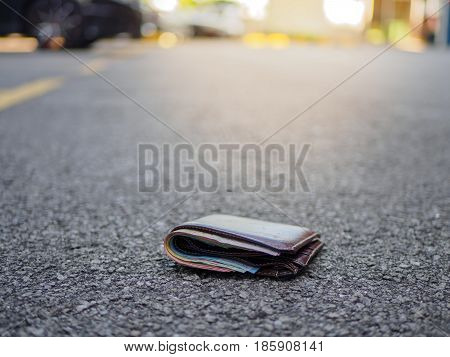 wallet with money drop on the street lost money concept copy space on top