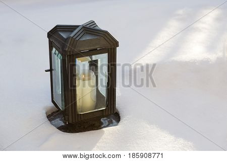 Eternal light at a grave in wintertime