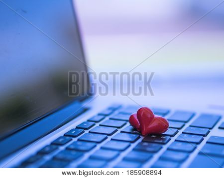 Red heart on the computer keyboard with sunlight and shadow. Internet dating copyspace Valentines day concept.