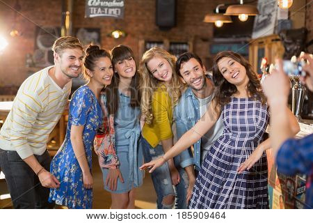 Group of happy friends posing while man photographing through mobile phone in pub