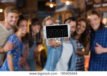 Group of friends taking selfie through mobile phone in pub