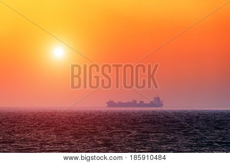 Alone barge in tranquil sea. Orange sky glowing by sunlight