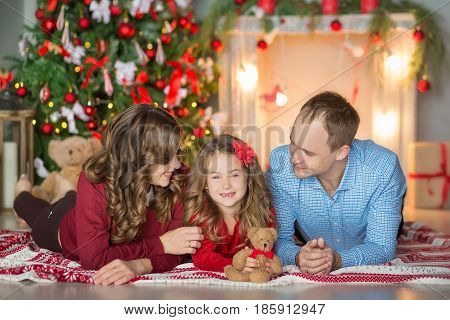 Family on Christmas eve at fireplace. Kids opening Xmas presents. Children under Christmas tree with gift boxes. Decorated living room with traditional fire place. Cozy warm winter evening at home