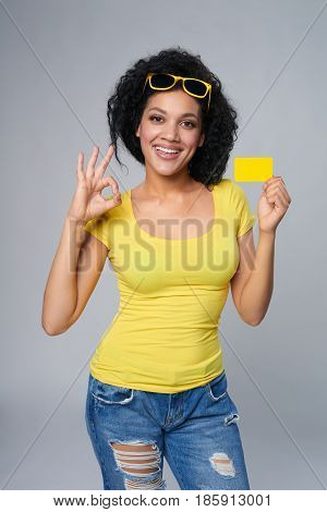 Smiling mixed race african american caucasian woman holding credit card and gesturing OK, isolated on grey background