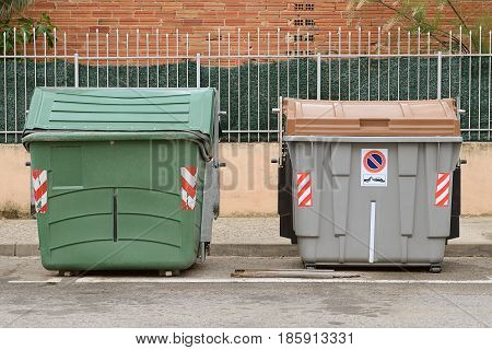 green and gray plastic garbage containers in the street