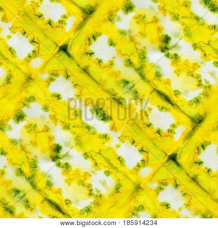 Seamless tie-dye pattern of yellow and green color on white silk. Hand painting fabrics - nodular batik. Shibori dyeing.