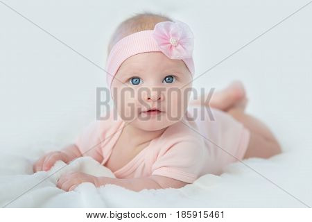 Portrait of adorable baby girl in pink dress.