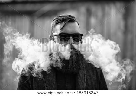 Vape Man. Outdoor Portrait Of A Young Brutal White Guy With Large Beard Letting Puffs Out Of Steam F