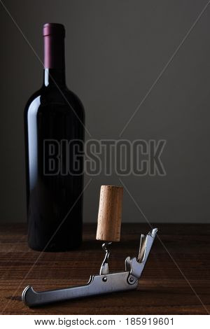 Closeup of a cork on a metal shiny cork screw with a bottle of wine in the background.
