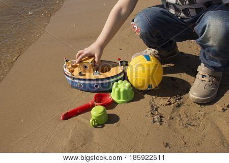 little boy with built sandcastle on beach