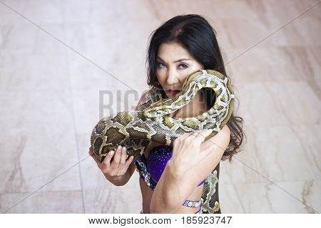 Adult woman in blue stage costume performs with big snake