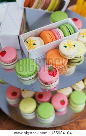 Beautiful Macarons choice. Plenty of colorful french cookies, meringue based confectionery desserts on serving plate at counter bar for sale. Pastel colors, packed in boxes and stacks, vertical image