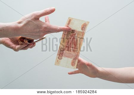 children's and woman's hand with stack of Russian money