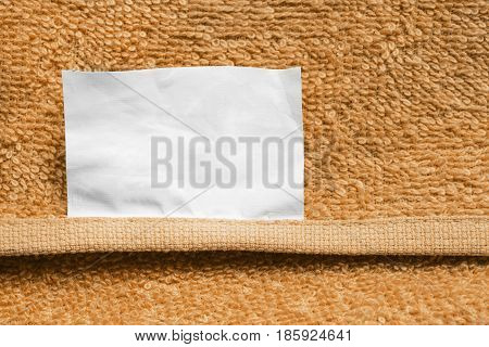 White blank clothes label on yellow terry towel as a background