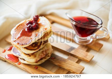 a stack of pancakes drizzled with berry jam