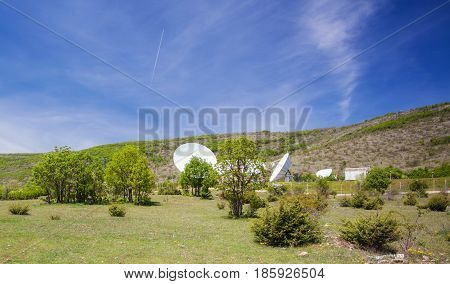 big satellite antennas on a field in the mountains