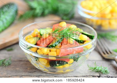Fresh vegetarian salad. Summer salad with cucumbers, tomatoes, corn, dill and olive oil and lemon dressing. Delicious and easy salad or side dish recipe. Fork, ingredients on a old wooden table