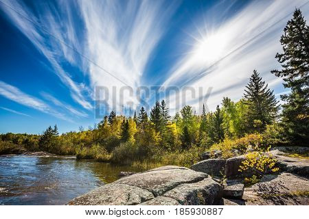 Incredible cirrus clouds  and huge flat stones in Old Pinawa Dam Park. Indian summer in Manitoba, Canada. The concept of ecological and recreational tourism