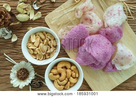 Roasted cashew nuts and peanuts and magenta crisp rice crackers appetizer in white bowl on wooden table.
