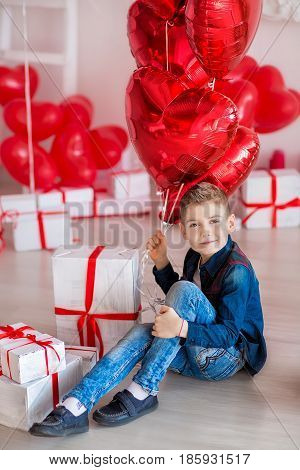 Handsome hipster teen posing with red heart baloon in studio. Young man in yellow shirt going to the date over studio background