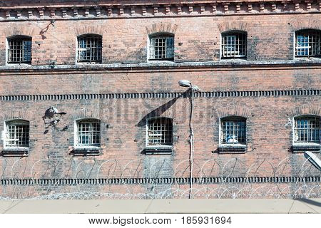 Wall Of Prison With Barred Windows