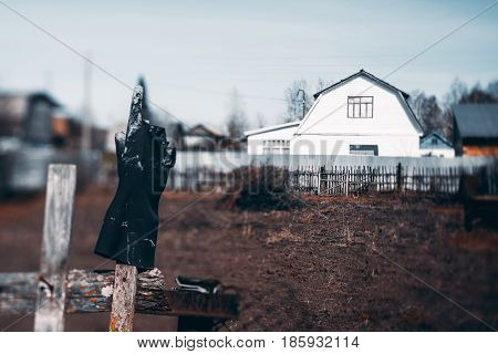True tilt-shift view of black rubber glove stained in paint worn on a wooden fence pointing to sky with forefinger and white two-storey summer house in background with empty garden in front of it