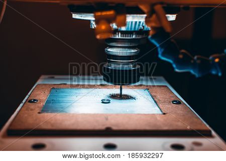 Close-up view of CNC milling machine cutting work piece of aluminum with high rotation speed in dark settings with copy space for young advertising text message or promotional content