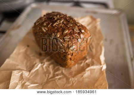 Fresh bread with sunflower seeds slice and cutting knife on rustic table