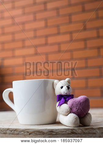 Teddy bear holding a purple heart. Teddy bear next to the white coffee Placed on a wooden desk. The backdrop is a brick block of brown.