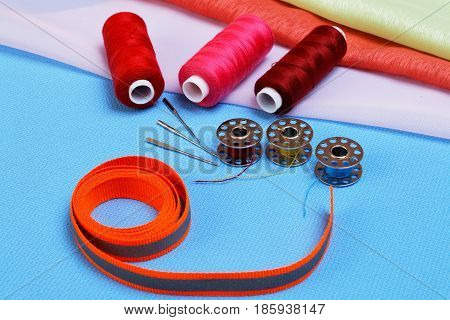 Various accessories for sewing on a sewing machine on a cloth background