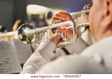 The trumpet in the hands of the musician in the orchestra closeup