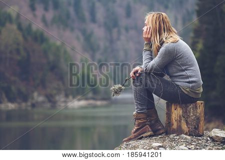 horizontal side view portrait of Caucasian young blonde woman with light colored sweater and jeans holding a tree branch and meditating relaxing alone on a tree stump in front of a lake surrounded by forest mountains copyspace