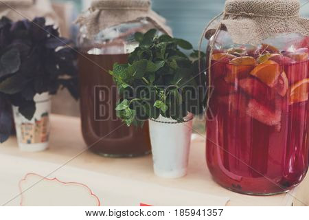 Closeup of craft lemonades in glass jars at restaurant background. Refreshing drinks in craft containers with sack on bar counter
