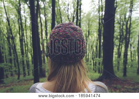 toned horizontal rear view portrait of Caucasian young woman with long blonde hair and colorful wool hat standing in a green forest