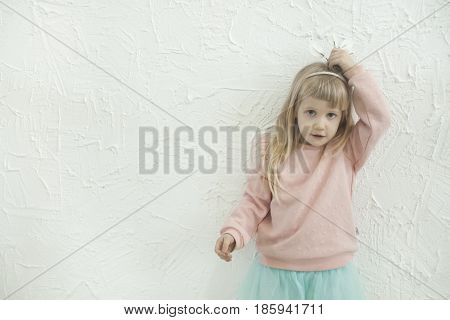Little princess girl making fun faces on the white brick wall backgtound, studio shoot, blank space