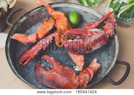 Grilled lobster claws at grill pan. Seafood delicacy barbecue outdoors. Picnic healthy food cooked at large metallic pan with lime. Mediterranean cuisine