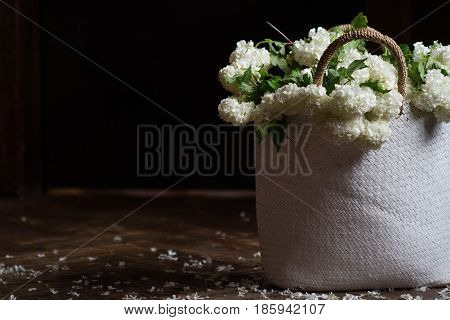 side view closeup of wicker bag with knitted handles full of white snowball flowers on dark wooden background in natural light copyspace on the right