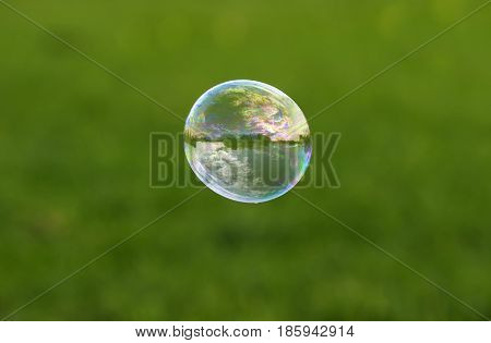 colorful soap bubble with reflection of the landscape and the sky flying on a bright summer meadow on a Sunny day
