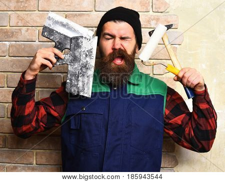 bearded painter man long beard brutal caucasian hipster with moustache in uniform holding various building tools: hammer roller paint spatulas with satisfied face on brick wall studio background