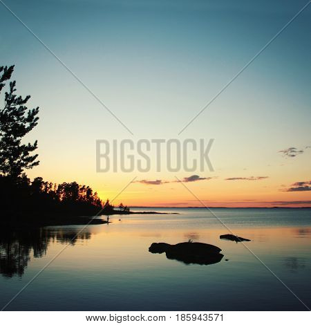 Wild nature of Russian North. Vintage photo. Beautiful northern landscape. Ladoga lake at sunset. Aged photo in retro style. Island of Valaam Republic of Karelia Russia.