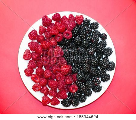 Fresh raspberries and blackberries on plate lined with symbol of yin and yang on red background, top view