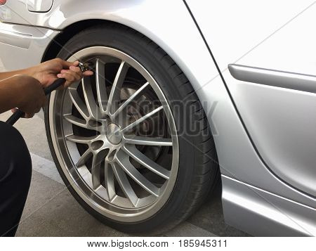 Man checking air pressure and filling air in the tires close up