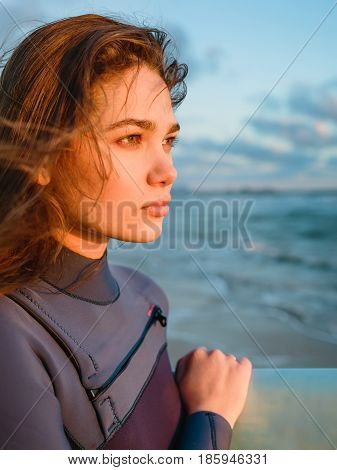 Young beautiful woman with long hairs in wetsuit. Girl posing with surfboard near ocean at sunset. Ready for surfing. Portrait